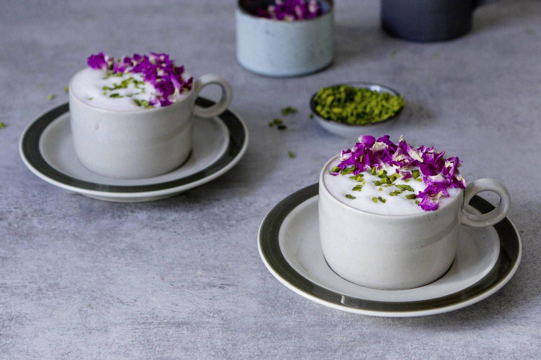 Hibiskusov latte serviran v dveh šalicah, okrašen s pistacijo in vijoličnimi cvetnimi listi