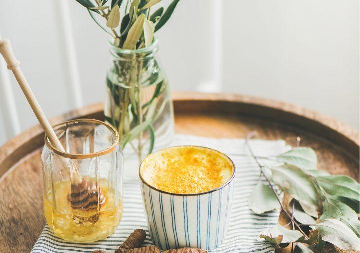 Tasse Golden Milk neben einem Honigglas