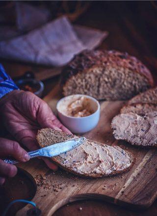 Brotstück, das mit Aufstrich bestrichen wird