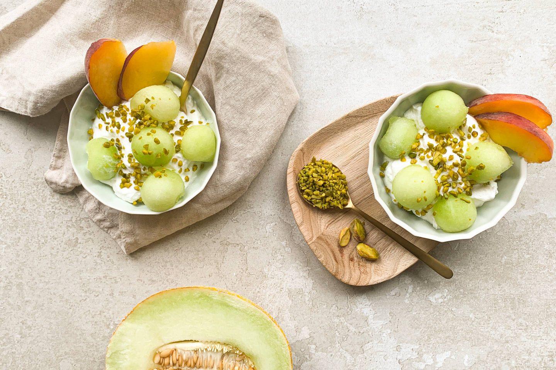 2 posodici melonininega jogurta obloženga z melono, breskvijo in posutega s pistacijo