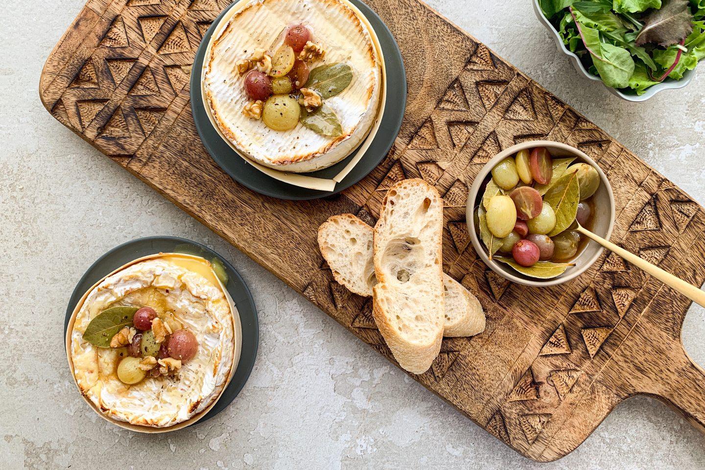 Kamember serviran na leseni rezalni deski, dekriran z glazirani grozdjem zraven posodo glaziranega grozdja in kruha