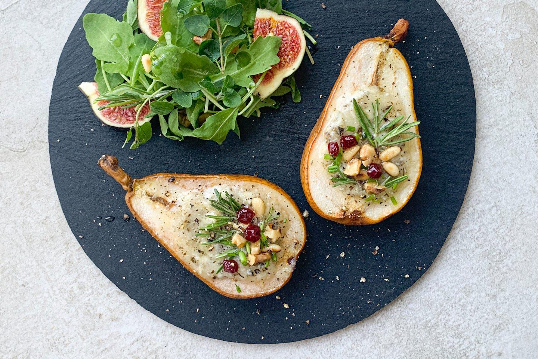 2 polnjeni hruški polnejeni z gorgonzolo in okrašeni s pinjolami in drobnjakom na črnem krožniku zraven solate in fig