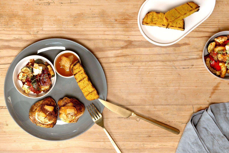 Piščanec pečen na havajski način serviran na krožiku skupaj s ploščicami polente in prilogo ratatoulille