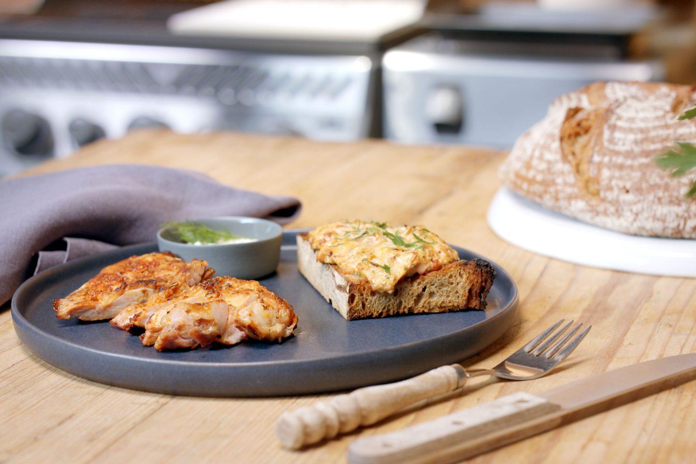Dimljena svinjina servirana na krožniku skupaj s popečenim kruhom
