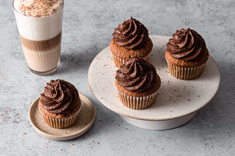 Lešnikovi muffini s kavnin nadevom na krožniku zraven kavnega napitka