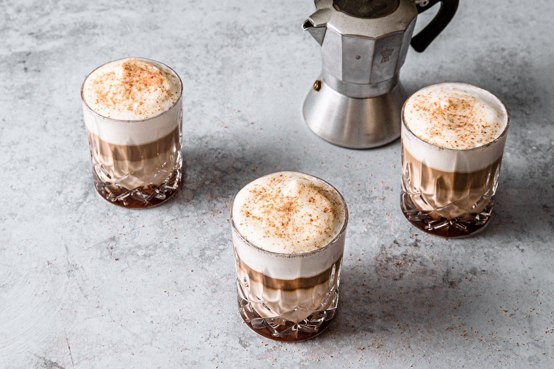 Kavni napitek s slano karamelo v treh kozarčkih zraven kuhalnika kave