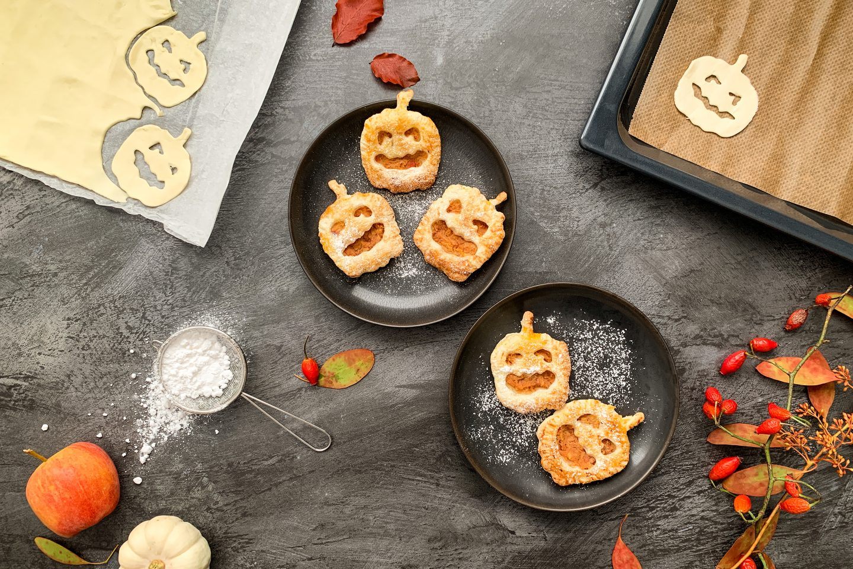 Jabolčni zavitki v obliki buč primerni za Halloween servirani na krožnikih zraven listnatega testa