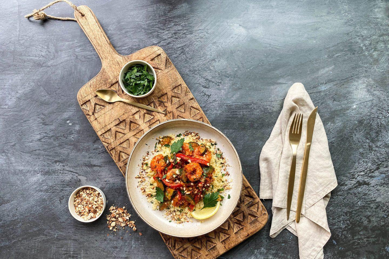 Kozice s hariso s kuskusom servirane na krožniku na rezalni deski zraven svežega koriandra