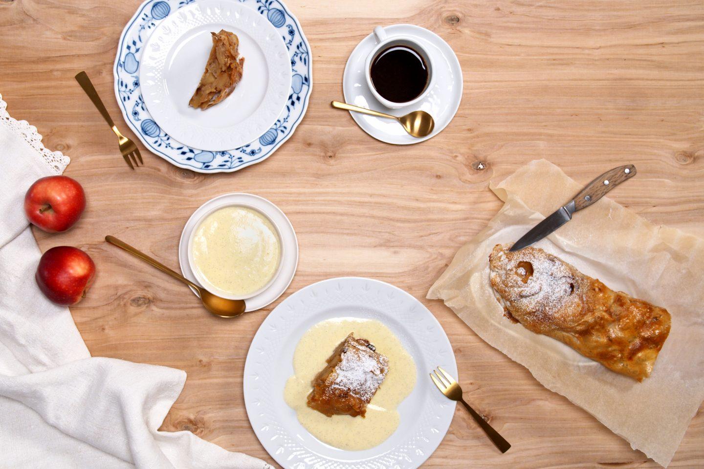 dva kosa jabolčnega zavitka, en serviran z vanilijevo omako in en brez nje, zraven celega pečenega zavitka, kave in svežih jabolk