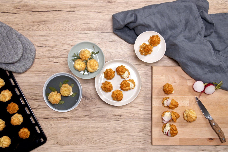 Princeske polnjene z začinjenim kremnim sirom na več krožnikih, rezalni deski ter sveže pečene na pekaču