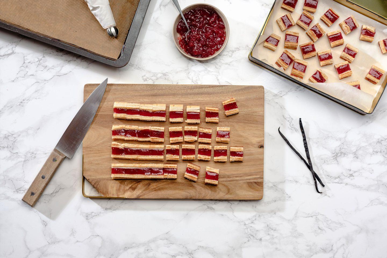 Sveže pečeni in narezani piškoti iz krhkega testa na rezalni deski zraven pladnja s piškoti in želeja iz rdečega ribeza