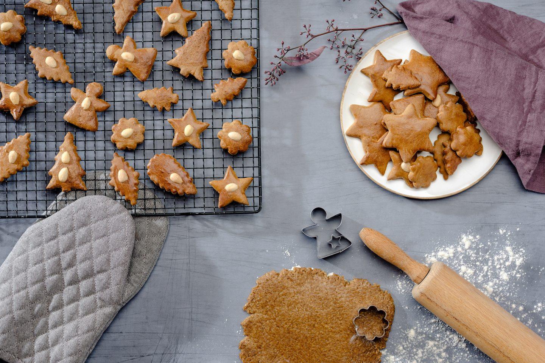 Medenjaki servirani na krožniku ter sveže pečeni na rešetki za pečenje zraven razvaljanega testa za medenjake