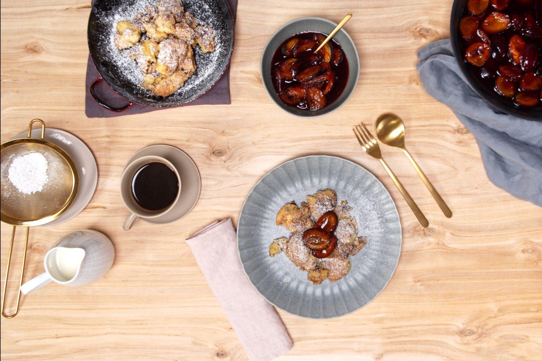Lesena mozi obložena z krožnikom carskega praženca z poprovimi slivami, krožnikom carskega praženca z posodo v kateri so pečene poprove slive ter kavo in mlekom