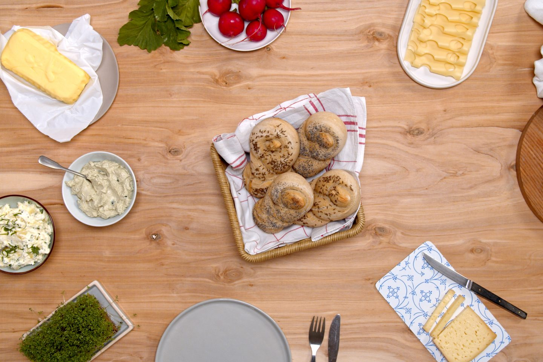 Pletenice z semeni v košari za kruh na sredini mize zraven raznih namazov in sira