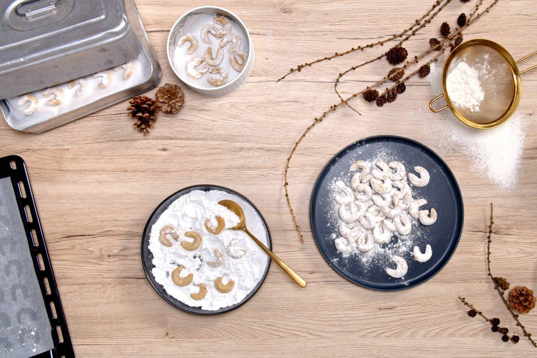 Vanilijevi rogljički na krožniku, zraven posode s sladkorem v prahu v katerem so svežo rogljički na mizi zraven pekača in posode za shranjevanje piškotov