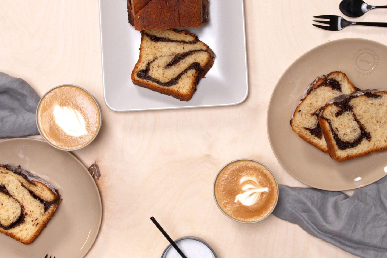 2 krožnika s kosi čokoladne pletenice na zraven cele sveže pečene pletenice in kave