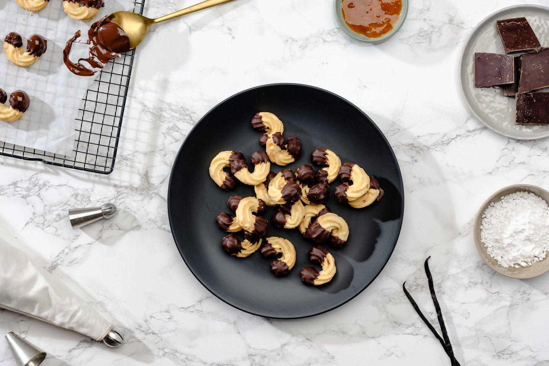 Brizgani piškoti na krožniku zraven sveže pečenih piškotov oblitih s staljeno čokolado na mizi z čokolado, želejem in sladkorjem v prahu