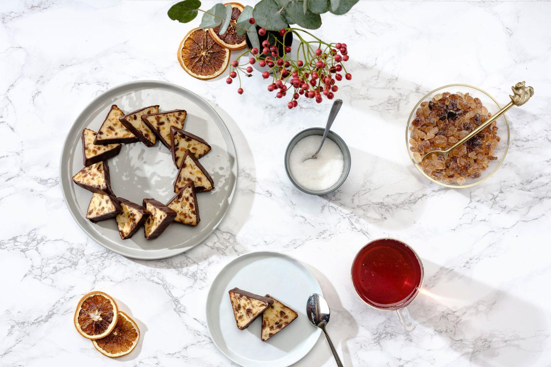 Čajni tirkotniki na pladnju zraven posušenega sadja, kandiranega sadja, sladkorja, čaja ter tveh rezin čajnega peciva na krožniku