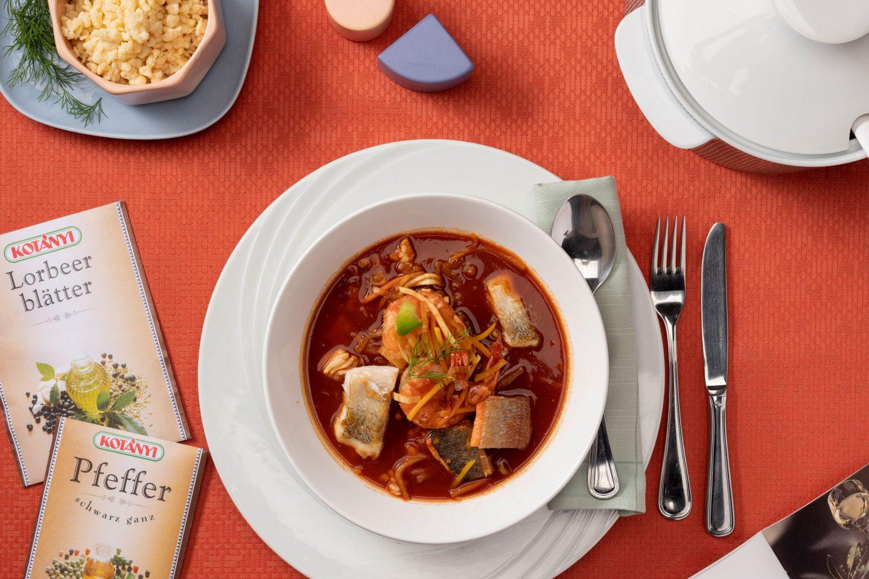 Ribe in morski sadeži v juhi iz paprike, ob njej pa vrečki lovorjevih listov in popra.