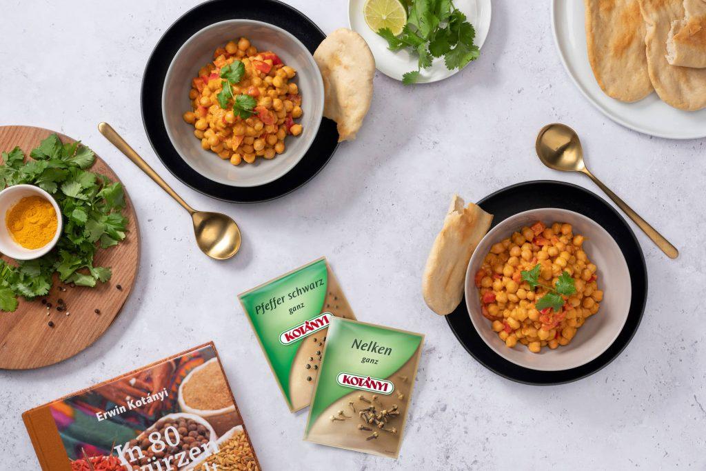 Čičerikin curry s kruhom naan, zraven pa vrečki črnega popra in celih klinčkov.
