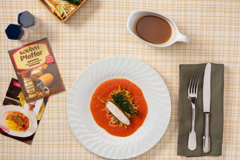 Zajčja pohrbtina na kremni omaki iz paprike z zelenjavo, zraven pa je embalaža belega popra.