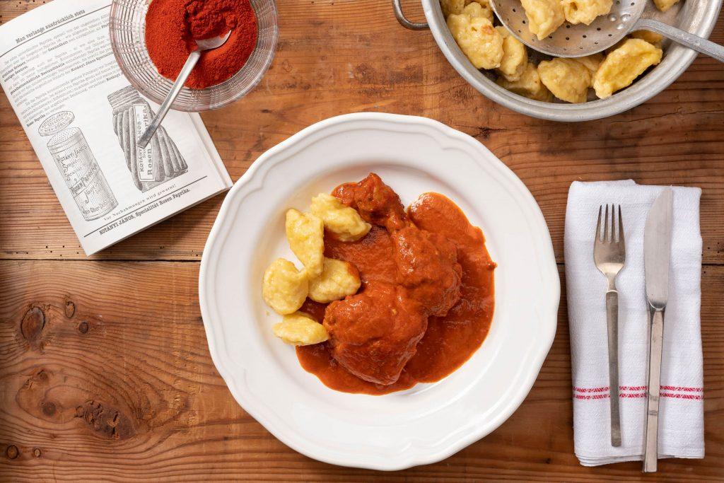 Globok krožnik s papriciranim piščancem in cmoki, zraven pa skleda, polna mlete paprike.